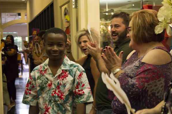 Terrien, a 13-year-old Southfield boy with a life-threatening renal disease, is cheered on by employees of BNP Media in Troy at a party given in his honor before he leaves on a trip to Spain, arranged by Make-A-Wish Michigan. Photo courtesy of Marie Sande