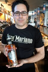 Francesco S. Viola with a bottle of his Luca Mariano Old Americana Bourbon at Plymouth's Cantoro Italian Market