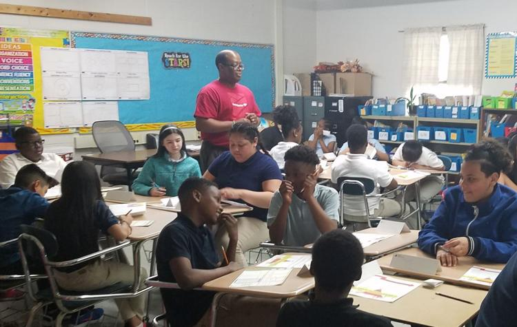 Bank of America employee volunteer Charles Tate teaches Pontiac sixth graders about financials.